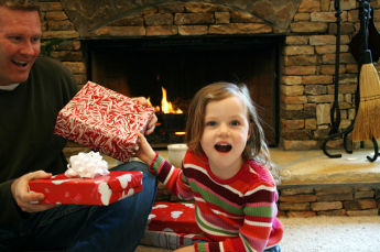 Happy girl getting present from Dad at Christmas.